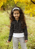 Little cute girl with dark curly hair sitting in the autumn forest — Stock Photo