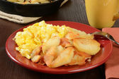 Scrambled eggs and home fries — Stock Photo