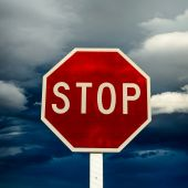 Roadside red stop sign on a cloudy background. — Stock Photo