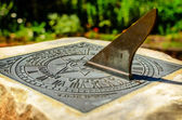 A brass sundial mounted on a stone plinth — Stock Photo