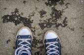 Blue sneakers shoes walking on concrete top view. — Stock Photo