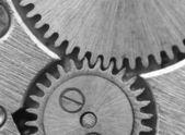 Fundo preto e branco com metais dentadas por um relógio. conceito — Fotografia Stock