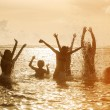 Silhouettes of people jumping in ocean — Stock Photo #71241953