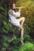 Beautiful dryad playing a flute — Stock Photo