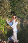 Beautiful woman dances in a lake with white veil — Stock Photo