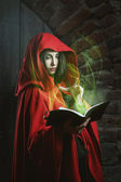 Red hooded woman with magical book — Stock Photo