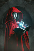 Red hooded woman casting powerful magic — Stock Photo