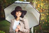 Beautiful woman with umbrella in autumn park — Stock Photo