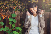 Gülümseyen genç kadın arasında sonbahar yaprakları — Stok fotoğraf
