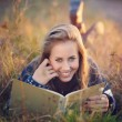 Beautiful blue eyes woman reading a book outdoor — Stock Photo #57540765