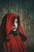 Dark red hooded woman in a misty forest — Stock Photo