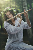 Dark forest nymph with a flute — Stock Photo