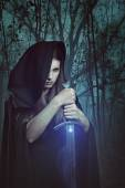 Beautiful woman with magic sword in a dark forest — Stock Photo