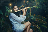 Beautiful forest nymph playing  flute with fairies — Photo