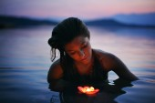Beautiful woman with floating candle — Stock Photo