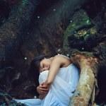 Постер, плакат: Beautiful dark woman sleeping among forest spirits