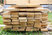 Boards in stack against house — Stock Photo