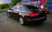 Mörk bil nära väggen med graffiti — Stockfoto