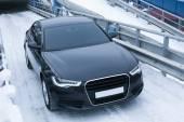 Black prestigious car on snow — Stock Photo