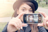 Woman photographing herself with phone — Stockfoto