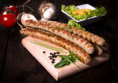 Grilled sausages on wooden board — Stock Photo