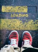 Mans legs behind loading sign — Stock Photo