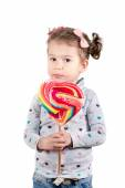 Child with big heart shape lollipop — Stock Photo