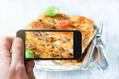 Man photographing lasagna with mobile phone — Stock Photo