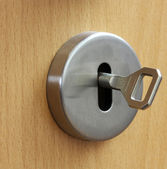 Closeup of an  keyhole with key on a wooden  door — Stock Photo