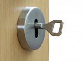 Loseup of an keyhole with key on a wooden  door. — Stock Photo