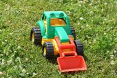 Toy green tractor on the grass. — Stock Photo