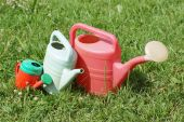 Three different sized watering can lie on the grass. — Stock Photo
