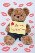 Teddy bear holding a yellow sign that says Be my Valentine — Stock Photo