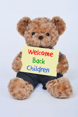 Teddy bear holding a Welcome back children sign — Stock Photo