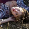 A girl lying in a grass on a field in a village — Stock Photo #55297133