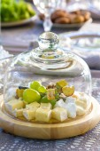 Cheese and grapes on a board under a glass hubcap — Stock Photo
