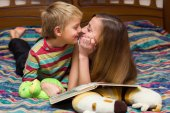 Boy and mother read a book lying on a bed — Stock Photo