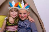 Girl and boy in carnival costumes indians studio — Stock Photo