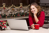 Woman with laptop in Christmas kitchen — Stock Photo