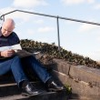 Man sitting on steps reading a newspaper — Stock Photo #52677609