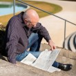 Man sitting on steps reading a newspaper — Stock Photo #52677687