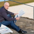 Man sitting on steps reading a newspaper — Stock Photo #52677879