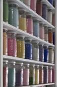 Shelving with glass jars of colorful pigments — ストック写真