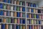 Shelving with glass jars of colorful pigments — Stock Photo