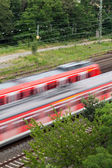 Fast moving trains with red stripe — Stockfoto