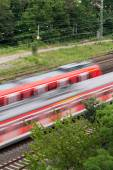 Fast moving trains with red stripe — Stock Photo