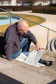 Man sitting on steps reading a newspaper — Stock Photo