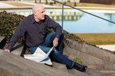 Man sitting on steps reading a newspaper — Foto de Stock