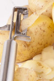 Potatoes with Peeler and Peeled Skin — Stock Photo