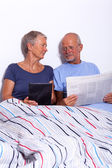 Senior Couple with Tablet and Newspaper — Stock Photo